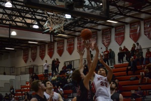 Jarius Hamilton (23) drives for a layup in the first half of Milan's 61-56 loss to Grosse Ile on Friday night. The senior forward led the Big Reds with 18 points.