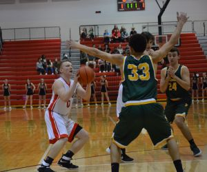 Trevor Ballard (left) pump-fakes in the first quarter of Milan's win over Flat Rock on Tuesday. Ballard led the contest in scoring with 15 points.